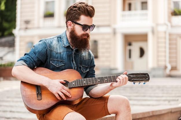 Musicien de rue. beau jeune homme barbu jouant de la guitare alors qu'il était assis à l'extérieur
