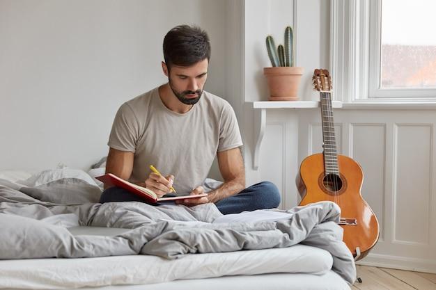 Musicien talentueux occupé écrit les mots d'une nouvelle chanson dans un cahier