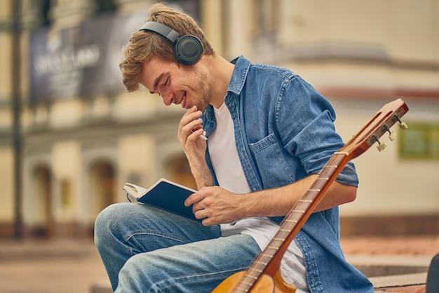 Un musicien talentueux et occupé écrit une nouvelle chanson dans un cahier