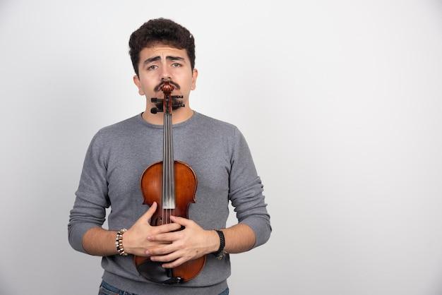 Un musicien tenant son violon en bois brun et semble stressé.