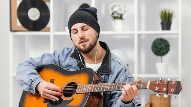 Musicien de tir moyen jouant de la guitare
