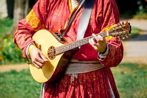 Musicien en vêtements lumineux médiévaux joue du luth