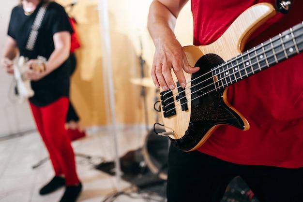 Musiciens jouant des guitares basses
