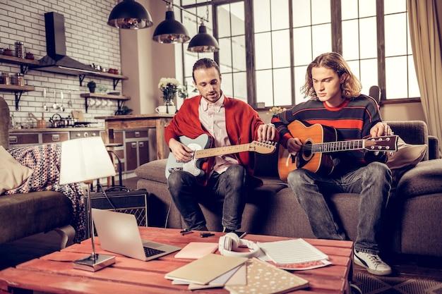 Des musiciens talentueux. de jeunes musiciens talentueux se sentent excités en jouant de la guitare assis sur un canapé à la maison