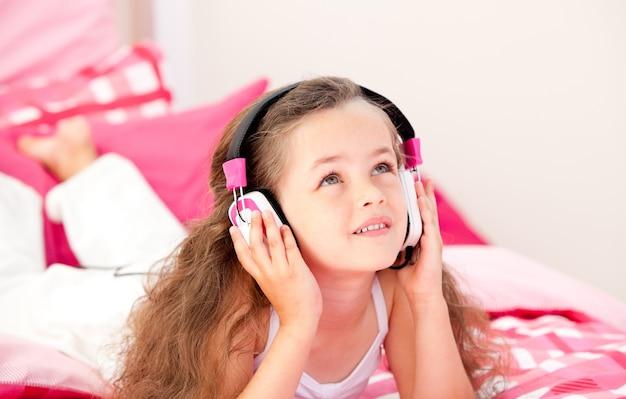 Musique écoute adorable petite fille allongée sur son lit