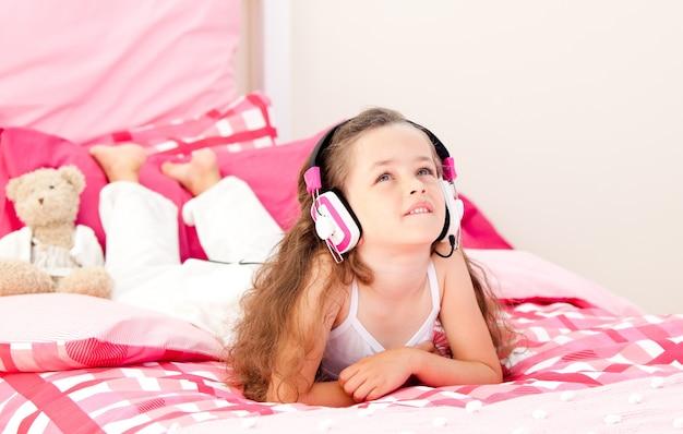 Musique écoute mignonne petite fille allongée sur son lit