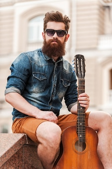 La musique c'est ma vie. confiant jeune homme barbu tenant une guitare et regardant la caméra alors qu'il était assis à l'extérieur