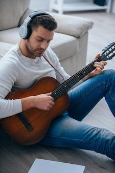 La musique fait partie de sa vie. vue de dessus du beau jeune homme au casque jouant de la guitare