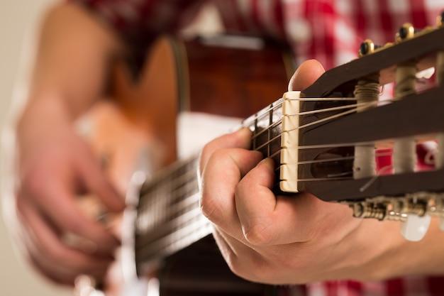 Musique, gros plan musicien tenant une guitare en bois