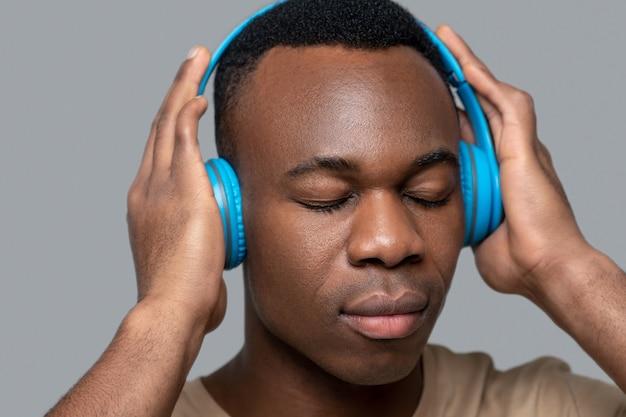 La musique. jeune homme à la peau foncée dans des écouteurs écoutant de la musique