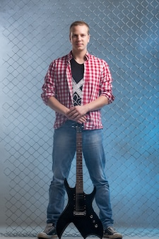 La musique. jeune musicien avec une guitare sur le mur de clôture