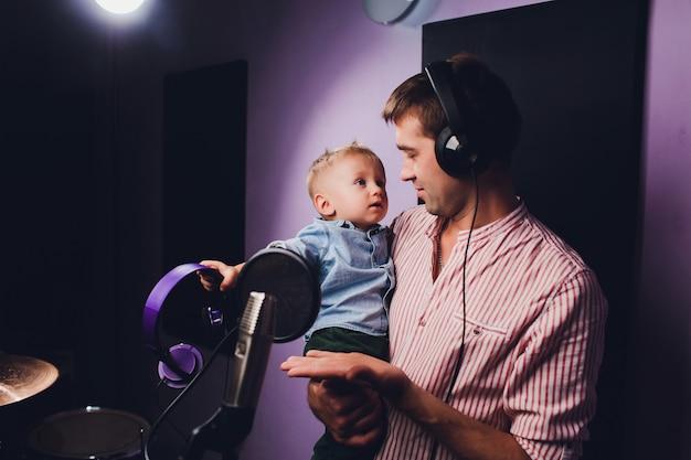 Musique, show-business, personnes et concept de voix - chanteur avec casque et microphone chantant une chanson au studio d'enregistrement sonore.