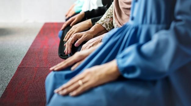 Musulmans en prière dans la posture de tashahhud