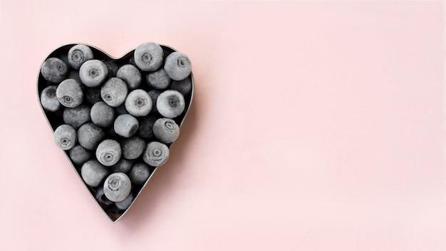 Myrtilles fraîchement congelées en forme de coeur en métal sur fond rose. cueillette de baies d'été. espace pour le texte.