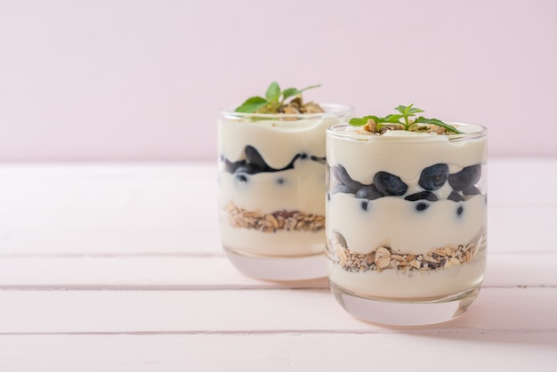 Myrtilles fraîches et yogourt avec granola - style d'alimentation saine
