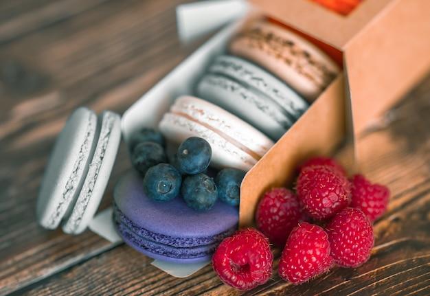 Myrtilles, framboises et biscuits macarons colorés dans une boîte en carton