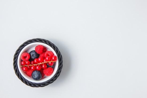 Myrtilles et framboises dans un bol avec vue de dessus de groseille