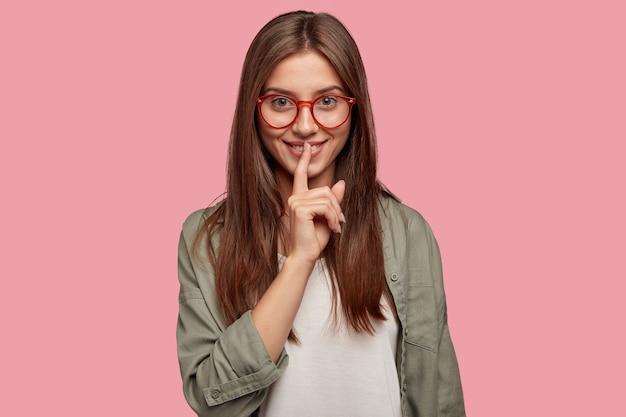 Mystérieuse belle étudiante posant contre le mur rose