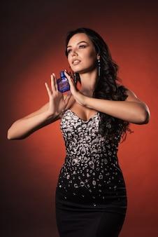 Mystérieuse belle jeune femme luxueuse dans une robe avec strass posant avec parfum