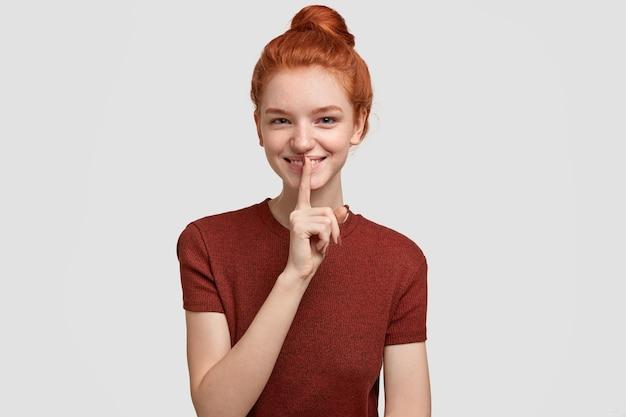 Mystérieuse fille aux taches de rousseur aux cheveux rouges heureux fait un geste chut, a une expression positive