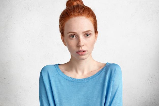 Mystérieuse magnifique jeune mannequin aux cheveux rouges attrayante avec une peau douce, porte un pull bleu lâche, regarde avec une expression confiante