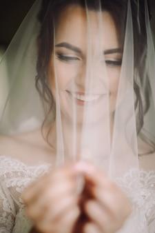 Mystérieux portrait d'une mariée cachée sous le voile et tenant une alliance