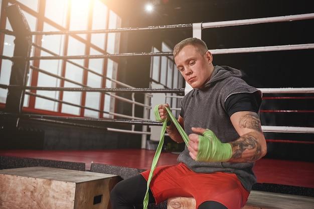 N'abandonnez jamais un athlète tatoué fort dans des vêtements de sport enveloppant les mains avec des enveloppements de boxe verts