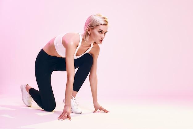 N'arrêtez pas la jolie et jeune femme blonde en vêtements de sport debout sur la ligne de départ