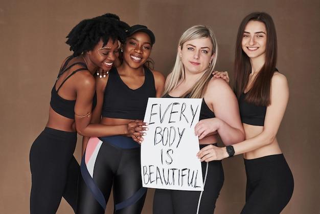 N'ayez pas peur d'être vous-même. groupe de femmes multiethniques debout contre l'espace brun