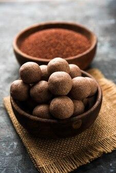 Nachni laddu ou ragi laddoo ou boules faites avec du millet, du sucre et du ghee. c'est un aliment sain de l'inde. servi dans un bol ou une assiette avec du cru entier et de la poudre. mise au point sélective