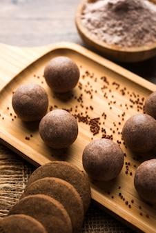 Nachni ou ragi laddu et biscuits ou biscuits à base de millet, de sucre et de ghee. c'est un aliment sain de l'inde. servi dans un bol ou une assiette avec du cru entier et de la poudre