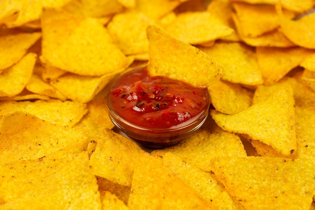 Nachos appétissants chips sur une assiette blanche et un gros plan de sauce épicée. triangles de tortilla jaunes.