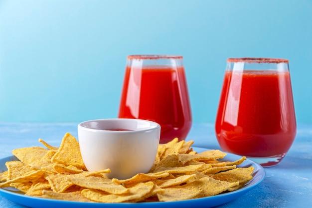 Nachos, chips tortilla de maïs avec sauce épicée et boisson alcoolisée michelada. cocktail avec jus de tomate et bière
