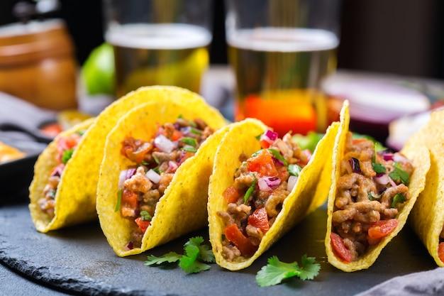 Nachos de croustilles de tortilla de maïs en coquille de taco avec du bœuf haché, de la viande hachée, du guacamole, de la salsa piquante au piment jalapeño et une sauce au fromage avec de la tequila ou de la bière sur une table.