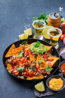 Nachos de croustilles de tortilla de maïs jaune avec boeuf haché, émincé, guacamole, salsa piquante au piment jalapeño et sauce au fromage avec tequila sur une table sombre.