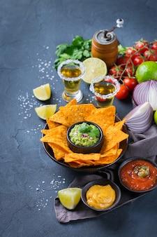 Nachos de croustilles de tortilla de maïs jaune avec guacamole, salsa de piment jalapeño rouge et sauce au fromage avec tequila sur une table sombre.