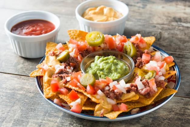 Nachos mexicains au boeuf, guacamole, sauce au fromage, poivrons, tomates et oignons en plaque sur table en bois