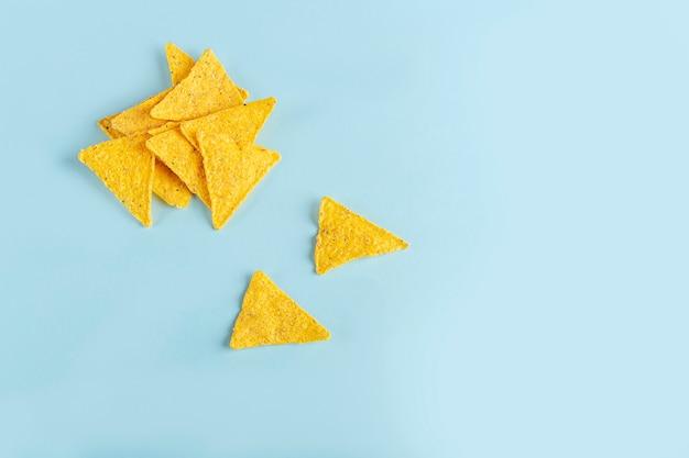 Nachos mexicains traditionnels, chips tortilla de maïs sur fond bleu.