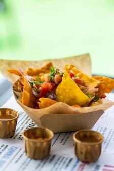 Les nachos de salsa sont sur un plateau dans une assiette en carton dans un café de la rue