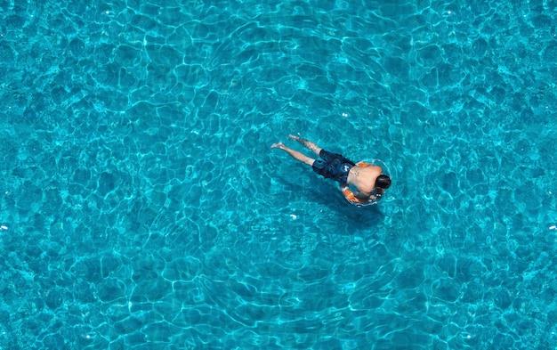 Nager dans la piscine de l'hôtel et l'eau de couleur bleu clair en été et vue d'angle supérieure.