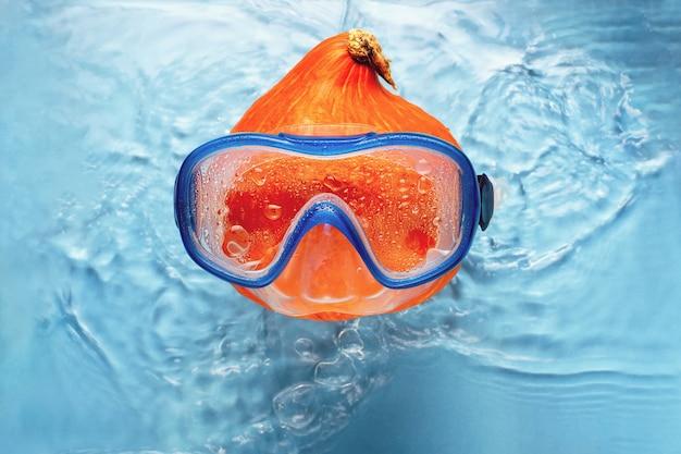 Nageur de citrouille orange dans un masque dans l'eau bleue concept halloween