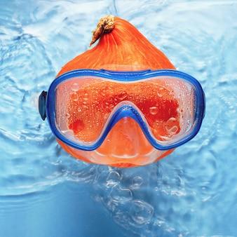 Nageur de citrouille orange dans un masque dans l'eau bleue