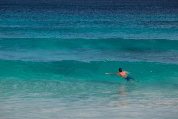 Nageur dans les vagues turquoise de l'océan indien