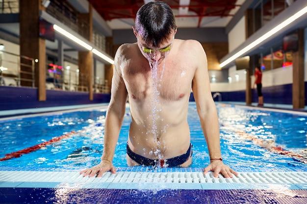 Le nageur émerge de la piscine d'eau avec des éclaboussures à l'intérieur