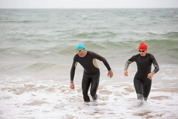 Nageurs en combinaisons de plongée dans les vagues de la mer