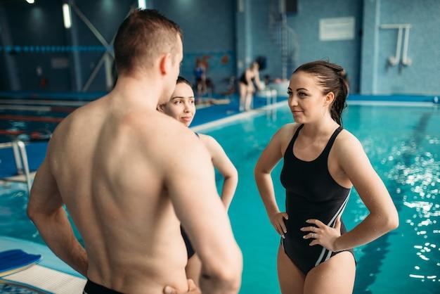 Les nageurs parlent de formation contre la piscine. formation d'aquagym, sports nautiques et mode de vie sain
