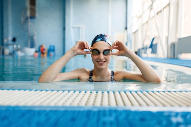 Nageuse en maillot de bain, bonnet de bain et lunettes pose dans la piscine