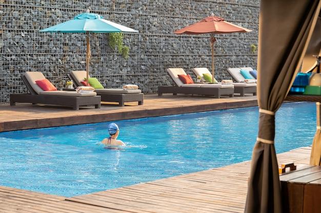 Une nageuse non identifiée porte une casquette en caoutchouc et fait de l'exercice dans la piscine.