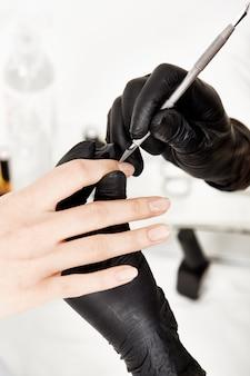 Nail artiste corrigeant la manucure avec un dissolvant pour cuticules en acier. traitements de beauté.