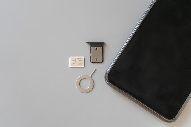 La nano-sim (4ff) usagée, le plateau retiré de la fente et l'extracteur pour extraire la carte sim et le smartphone sont sur la table